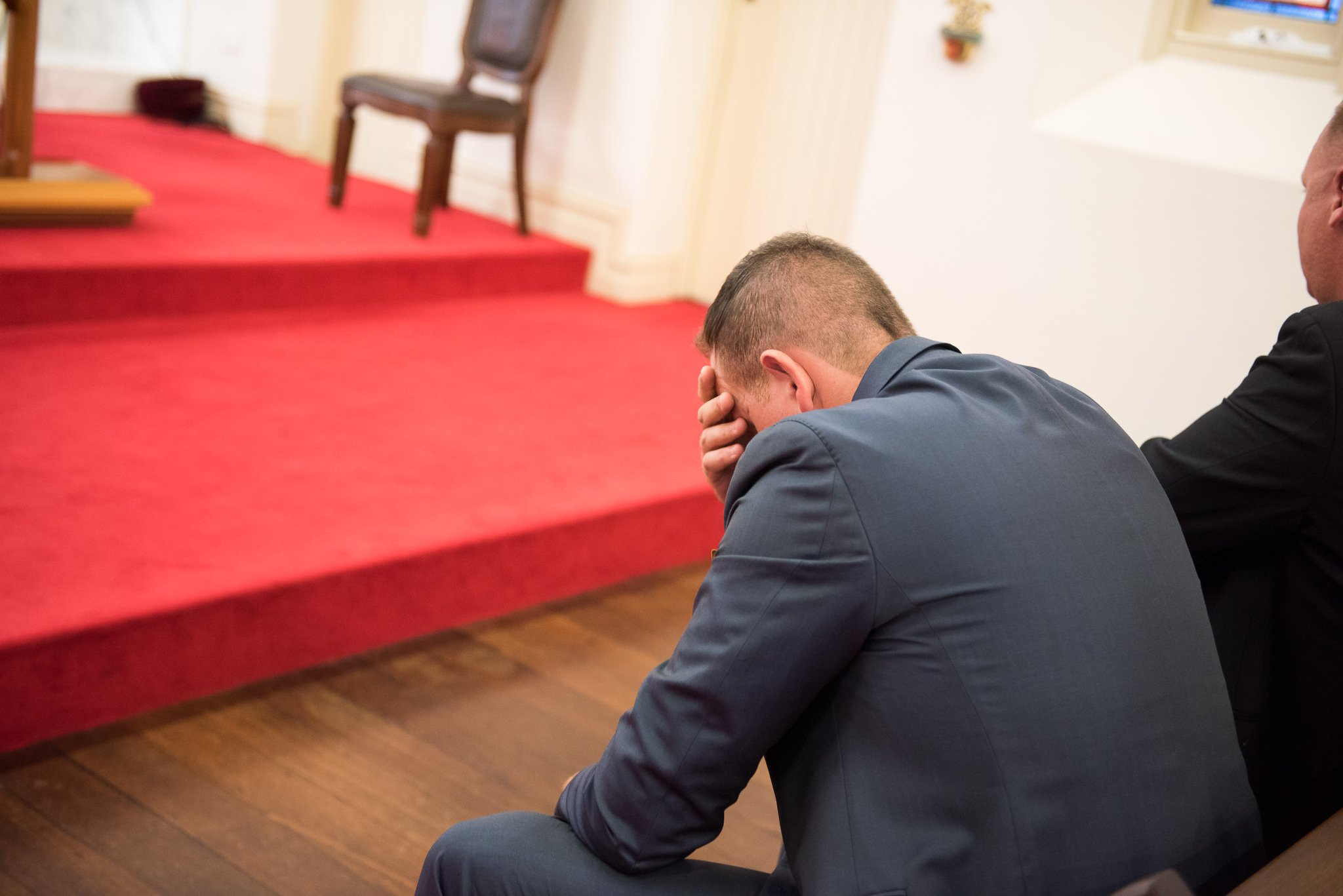 groom holding his head waiting