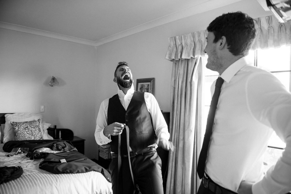 Groom getting ready laughing