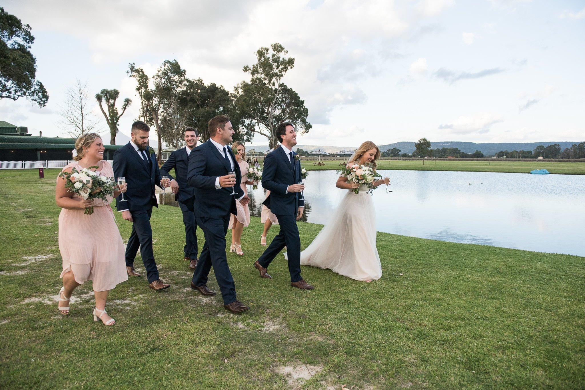 bridal party walking by a lake