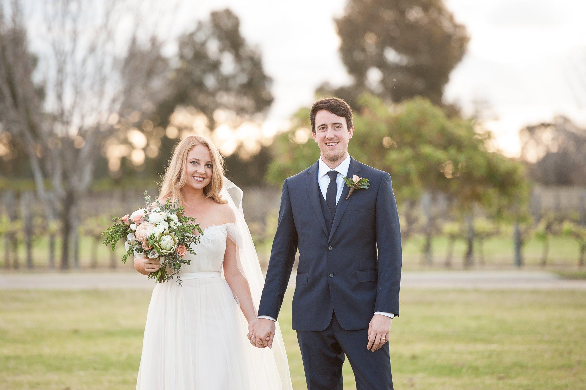 Bride and groom holding handsin soft light