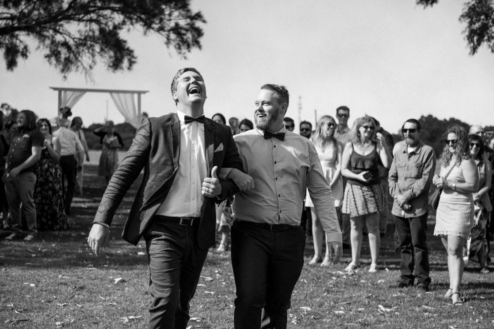 groomsman and bridesman laughing